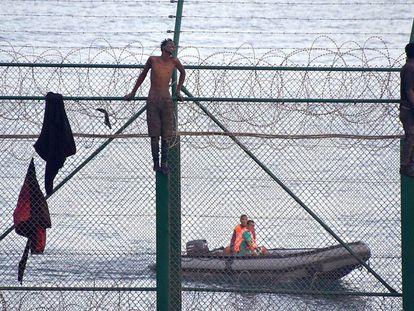 Migrants jump the border fence into Ceuta.