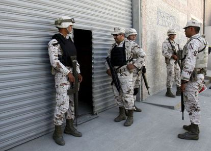 Soldiers guard the entrance of the warehouse where the secret tunnel was being constructed.