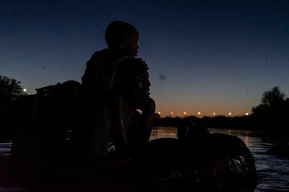 A Haitian man and his son crossing the Rio Grande from Ciudad Acuña (Coahuila) to Del Río (Texas).