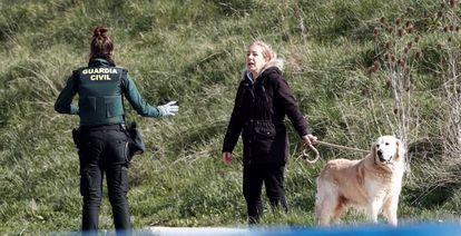 A Civil Guard officer informs a dog owner of the lockdown rules.