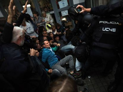 National Police officers remove members of the public from the Jaume Balmes school in Barcelona.