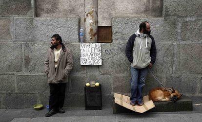 Two homeless men on the street in Madrid.