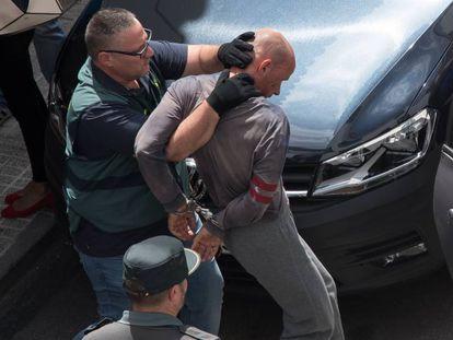 The suspect, Thomas Handrick, is taken into custody.