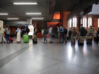 Passengers wait in line for a train at Madrid's Atocha station on Friday afternoon.