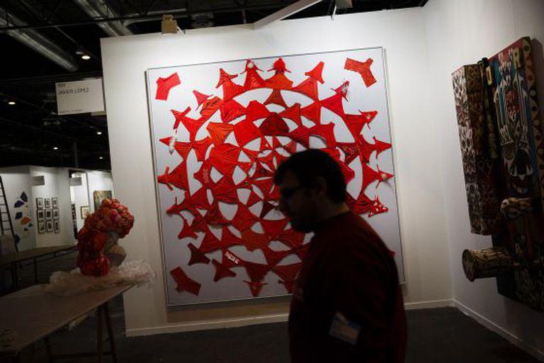 An art dealer walks through the stands at Arco.