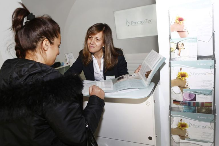 An employee talking to a client at a Madrid fertility clinic.