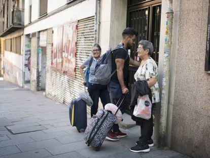 Tres personas llegando a un piso de alquiler turístico.