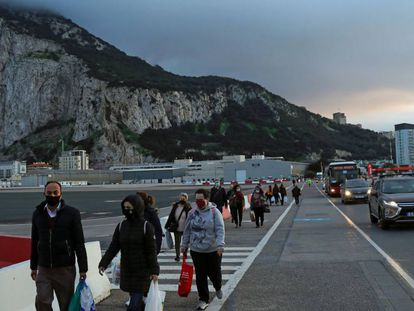 People walking along the Gibraltar airport runway to reach the border with Spain.