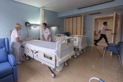 Two healthcare workers prepare a room in the Hospital Universitario Morales Meseguer in Murcia, after the last coronavirus patient there was discharged.