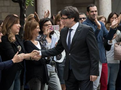 Catalan regional premier Carles Puigdemont greets his employees the day after the referendum.