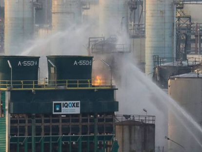 Firefighters work to put out the blaze at the chemical plant (Spanish text).
