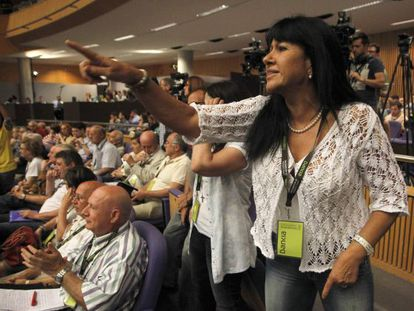A woman shouts at Bankia Chairman José Ignacio Goirigolzarri as he delivers a speech during the annual shareholder meeting.