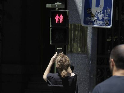 Passersby taking pictures of the new traffic lights in Madrid.