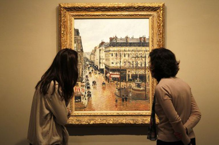 Thyssen museum visitors contemplate Pissarro's Rue Saint-Honoré in the Afternoon. Effect of Rain (1897).