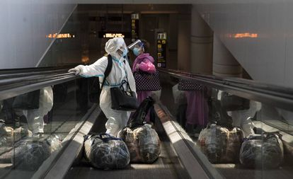 Two women arrive at El Prat airport in Barcelona on Sunday.