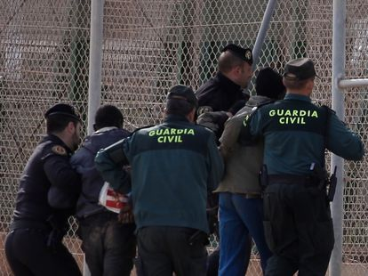 Civil Guard officers removing two migrants who had jumped the border fence in Melilla in 2014.