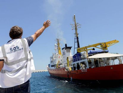 An NGO worker waves to the 'Aquarius' as it leaves Spain.