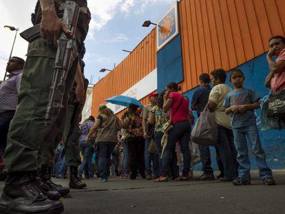 People stand in line outside a supermarket in Venezuela.