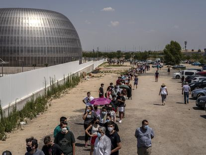 People wait in line outside the Hospital Enfermera Isabel Zendal in Madrid on Tuesday for their Covid-19 vaccines.