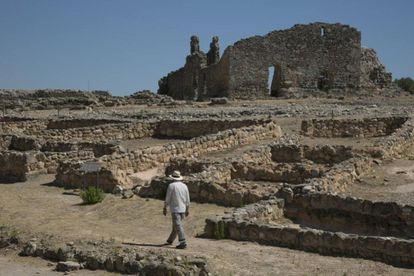 An archaeologist walks around the remains of shops and the homes of nobles.