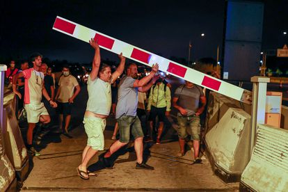 People lifting the toll barriers on the C-32 road.