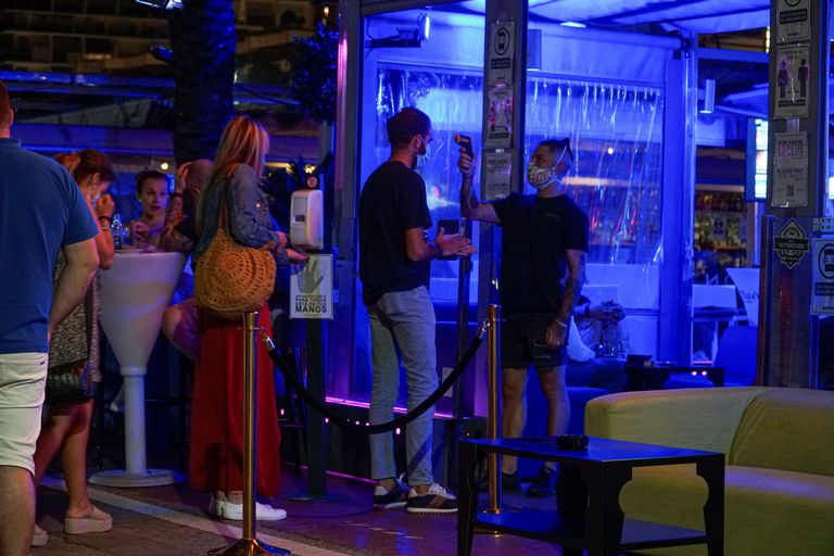 A temperature check is carried out at the door of a bar in Marbella, in southern Spain.