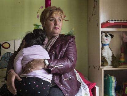 Justi Carretero holds her foster daughter in her house in Guadalajara.