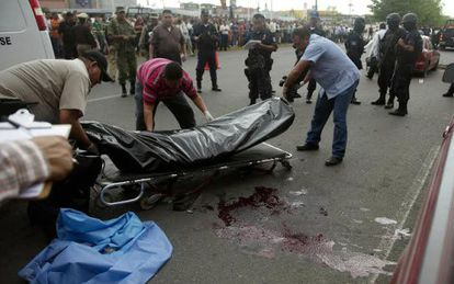 Forensic experts transfer the bodies of two police officers murdered in Culiacán.