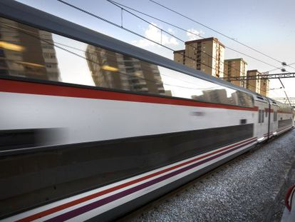 A train rushes by housing in Catalonia.