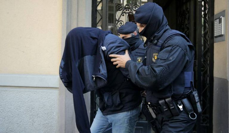Two Mossos take off a suspect of Brussels terror attacks in Barcelona.