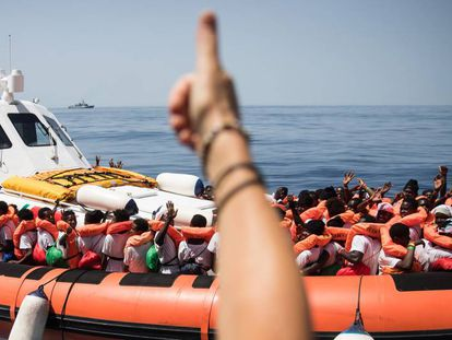 Migrants are moved from the 'Aquarius' to another boat that will travel to Spain.