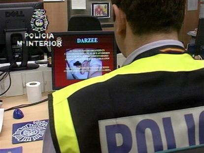 An officer from the Technology Investigation Brigade analyzes seized child pornography material .