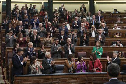 Socialist deputies applaud the finance minister during the budget debate.