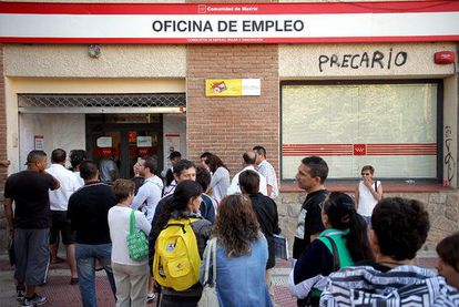People lining up in front of an unemployment office.