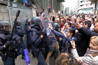 Voters at a school in Girona clash with riot police who were trying to seize ballot boxes.