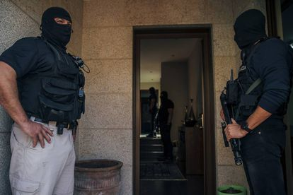 Officers guard a house in Pontevedra while their colleagues search inside.