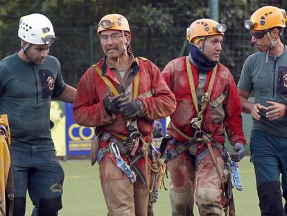 Two of the four cavers are accompanied by their rescuers.