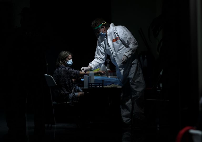 A health worker takes a blood sample from a woman at the Arts Center Auditorium in Arroyomolinos, Madrid.