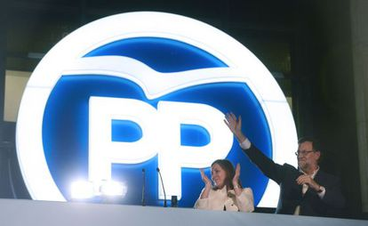 Prime Minister Mariano Rajoy waves next to his wife Elvira Fernandez at PP headquarters on Sunday night.