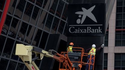 Workers putting up a CaixaBank sign at Bankia headquarters in Madrid's Puerta de Europa towers following the merger.
