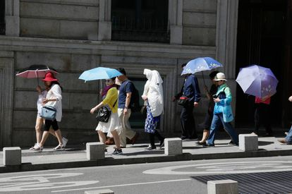 Tourists use umbrellas to keep the sun off in Madrid.
