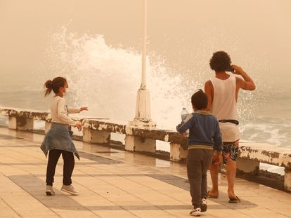 A family watches the waves during a sandstorm in the Canary Islands.