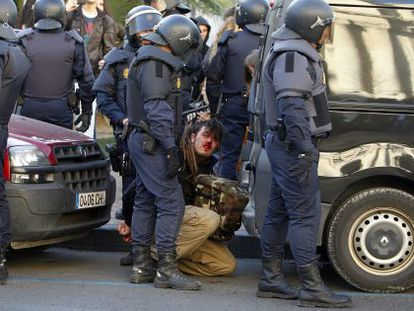 A bloodied protestor is detained by police in Valencia on Monday.