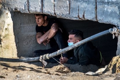 Migrants in Ceuta hide from police in between sewage pipes on May 23.