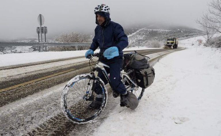 A cyclist tries to negotiate snowy roads in Lugo province.