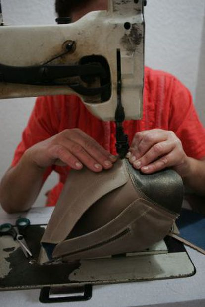 A woman stitches a boot in an illegal workshop in Alicante.
