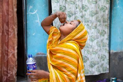 A tuberculosis patient takes her medication at home in Dhaka, Bangladesh.