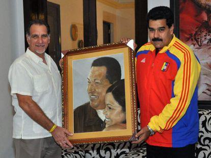 René González and Maduro hold a portrait of the late Chávez