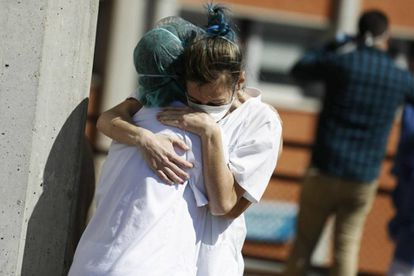 Two health workers hug outside the Severo Ochoa hospital in Madrid.
