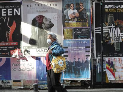A woman in Madrid passes by posters advertising concerts that have been canceled due to the coronavirus crisis.